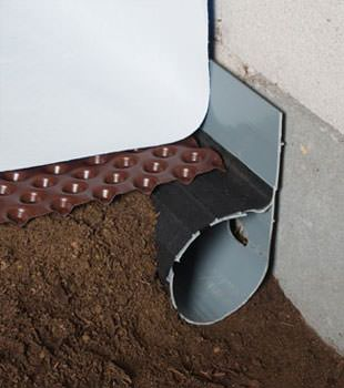 Closeup of a crawl space drainage system installed in Annandale